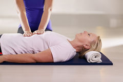 Young therapist doing reiki therapy to senior woman Stock Images