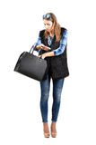 Young trendy woman searching for something in her handbag Stock Photos