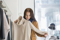Young woman choosing sweater in store Royalty Free Stock Photos