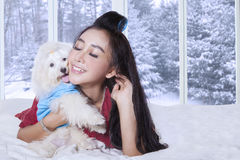 Young woman and her puppy lying on bed Stock Images