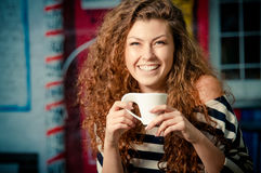 Young woman holding cup of coffee outside cafe Royalty Free Stock Image