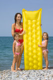 Young woman and little girls standing on beach Royalty Free Stock Image