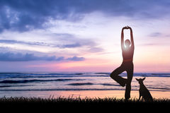 Young woman practicing yoga at beach on sunset Stock Photo
