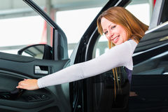 Young woman in seat of auto in car dealership Royalty Free Stock Photos