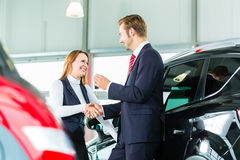 Young woman and seller with auto in car dealership Stock Photos