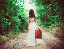 Young woman with suitcase in hand going away by rural road Stock Images
