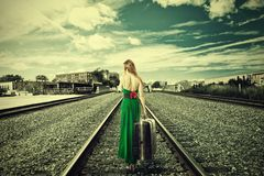 Young woman with suitcase walking away on rail tracks Royalty Free Stock Photo